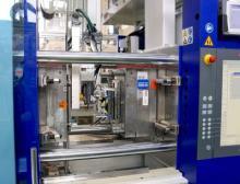 Beide Spritzgießmaschinen sind mit Rolle-zu-Rolle-Folienvorschubeinheiten ausgerüstet. Die Roboter tragen eine Folien-Wärmeplatte und gegenüber davon den Sauggreifer zur Fertigteil-Entnahme