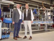 Thomas Bertram und Dirk Wevelsiep vor der verketteten Spritzgießanlage